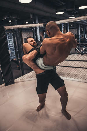 Two men in gloves and shorts are fighting in cage using grappling Reklamní fotografie - 111481364