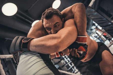 Dos hombres con guantes de boxeo y pantalones cortos están peleando en la jaula usando la técnica de agarre Foto de archivo
