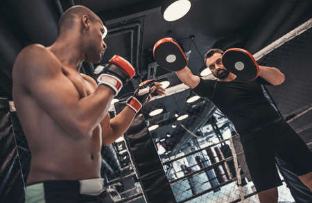 Afro American boxer in gloves is training with a coach in the boxing ring