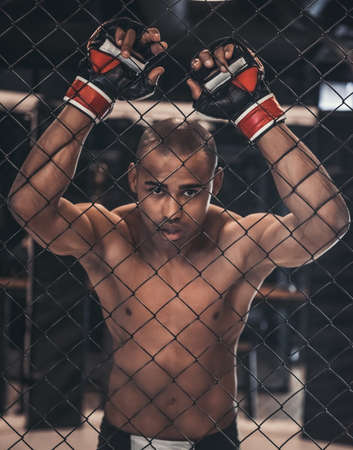 Tired Afro American fighter in gloves is leaning on the net of the cage Reklamní fotografie