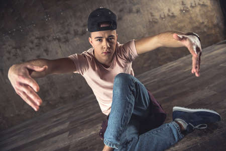 Young man break dancing on the wall background, performing tricks