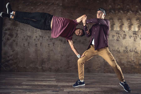Young men break dancing on the wall background, performing tricks Stok Fotoğraf