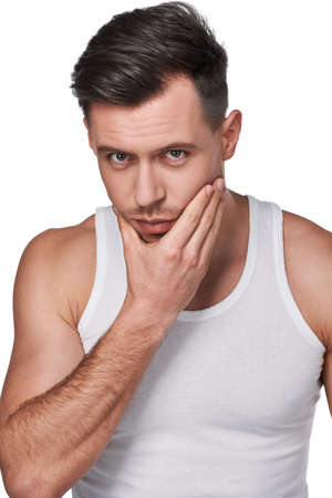 Men's beauty. Skincare. Portrait of handsome man touching his cheek and looking at camera, isolated on white