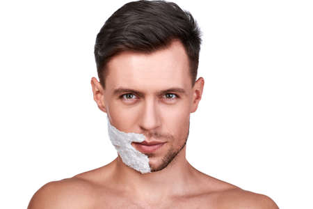 Mens beauty. Portrait of handsome man with shaving foam on the half of his bristled face, isolated on white