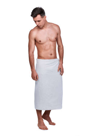 Mens beauty. Full-length portrait of handsome man wrapped in towel, isolated on white