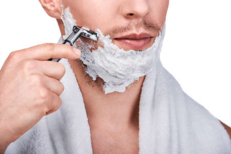 Men's beauty. Cropped image of handsome man shaving with a razor, isolated on white 免版税图像