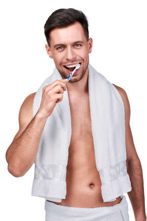 Dental care. Portrait of handsome man wrapped in towel brushing his teeth, isolated on white