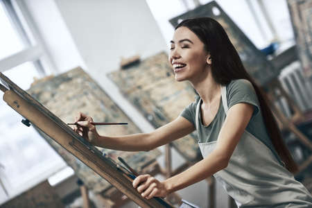 Young beautiful woman painting artist while working in a studio, smiling to the camera
