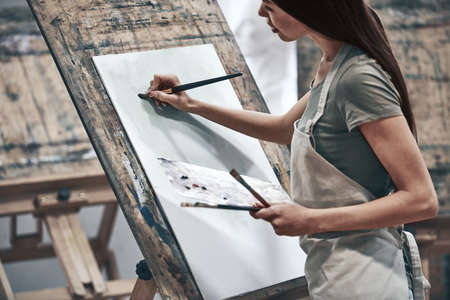 A young beautiful woman is a painting artist while working in a studio