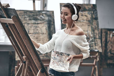 Young beautiful woman painting artist while working in studio, listening to music in headphones