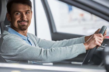 Young man is sitting in the car in the showroom. Stockfoto