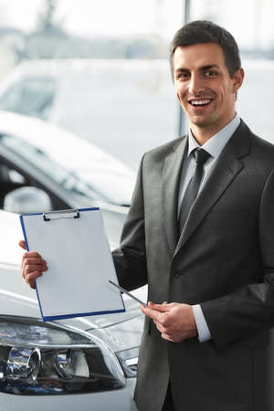 Young man is holding a contract in a dealership. Stockfoto