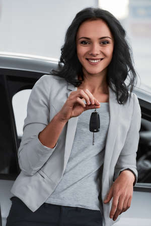 Happy young woman is holding keys to new car and looking at the camera.
