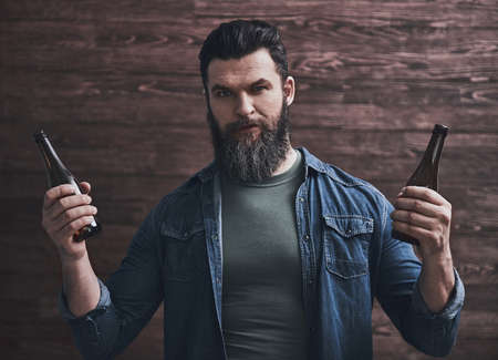 Bearded man is holding two bottles of beer, on a wooden background