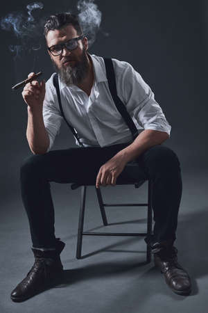 Stylish bearded man in suspenders is smoking a cigar, sitting on the chair, on dark background