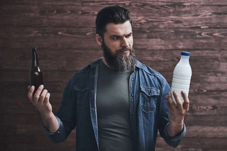 Bearded man is holding a bottle of milk in one hand and beer in another, on a wooden background