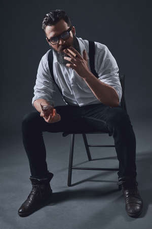 Stylish bearded man in suspenders is smoking a cigar and holding a glass of whiskey, sitting on the chair, on dark background