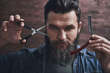 Bearded man is holding razor and scissors and looking at camera, on a wooden background