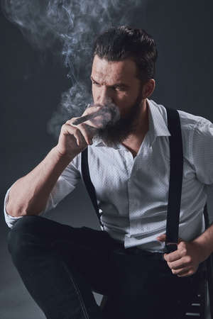Stylish bearded man in suspenders is smoking a cigar, on dark background
