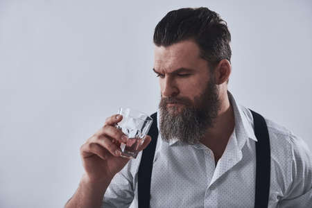 Bearded man in shirt with suspenders is holding a glass of whiskey, on a light background Zdjęcie Seryjne - 123107521