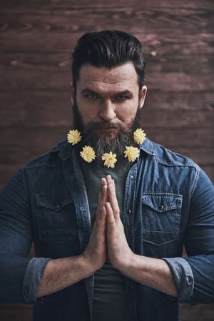Man, his beard decorated with yellow flowers is holding palms together and meditating, on a wooden background Zdjęcie Seryjne
