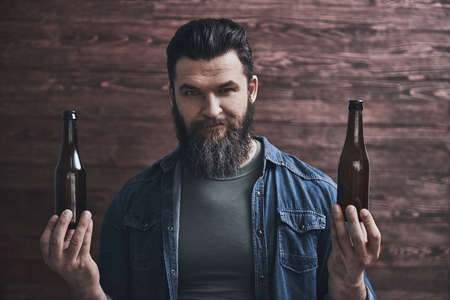 Bearded man is holding two bottles of beer, looking at camera and smiling, on a wooden background Zdjęcie Seryjne - 123107550