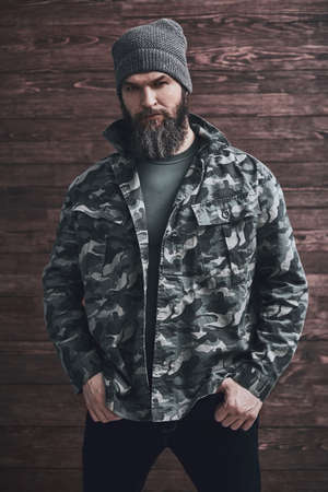 Style. Bearded man in camouflage jacket is looking at camera while standing with his hands in pockets on a wooden background