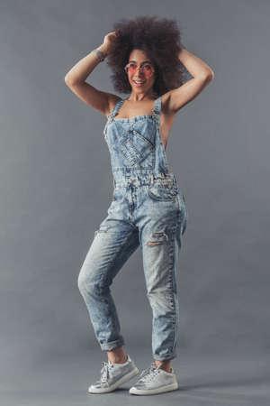 Mujer afroamericana en overoles de mezclilla está posando en la cámara y sonriendo, sobre un fondo gris, de cuerpo entero Foto de archivo
