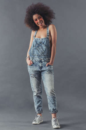 Afro American woman in jean overalls is posing at camera and smiling, on a grey background, full-length Reklamní fotografie