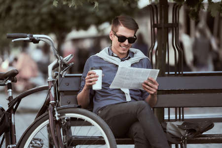 Young handsome man with bicycle sitting on the bench and resting.