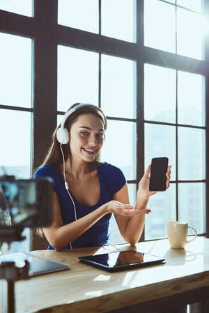 Young beautiful girl blogger working in office while shooting at camera listens to music in headphones