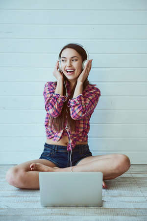 Portrait of a young beautiful girl with long hair uses a laptop and listens to music in headphones while sitting on the floor