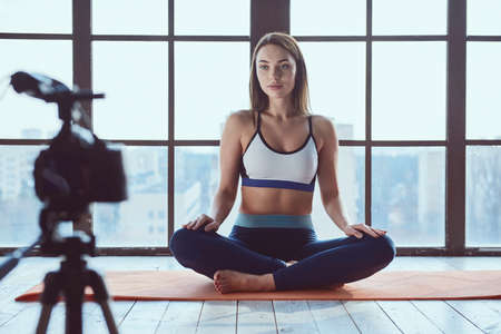 Young beautiful girl blogger while shooting fitness workout at home on big window background