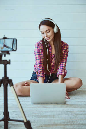 Portrait of a young beautiful girl blogger with long hair uses a laptop and listens to music in headphones while sitting on the floor taking pictures for a blog