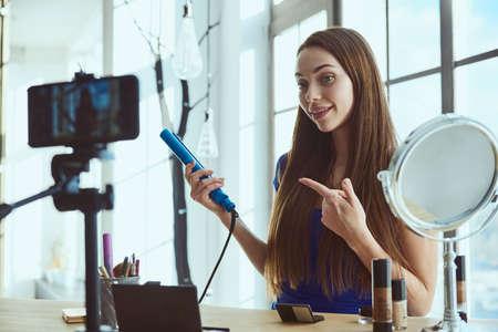 Young beautiful woman blogger using hair iron while shooting at camera at home