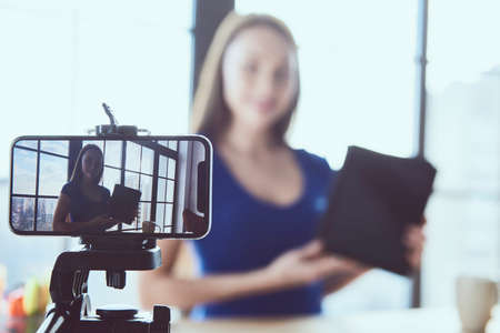 Young beautiful girl blogger working in office while shooting at camera