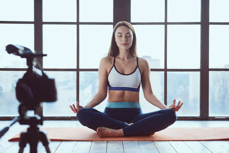 Young beautiful girl blogger while shooting fitness workout at home on big window background Zdjęcie Seryjne - 129440824