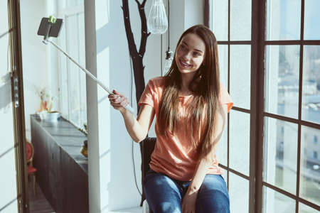 Young beautiful woman blogger while shooting selfie on phone using monopod sitting near window at home