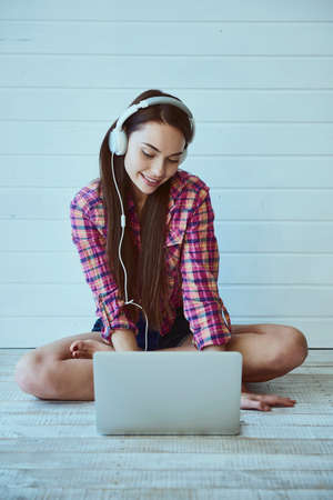 Portrait of a young beautiful girl with long hair uses a laptop and listens to music in headphones while sitting on the floor Zdjęcie Seryjne - 129441336