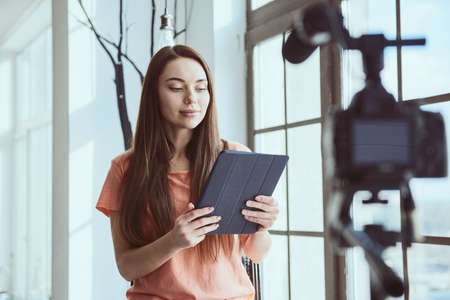 Young beautiful happy woman blogger uses tablet while shooting selfie on camera at home