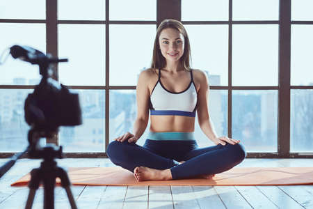 Young beautiful girl blogger while shooting fitness workout at home on big window background Zdjęcie Seryjne - 129441385