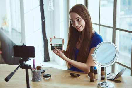 Young beautiful woman blogger using cosmetics while shooting at camera at home