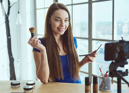 Young beautiful woman blogger using cosmetics while shooting at camera at home Zdjęcie Seryjne - 129441404