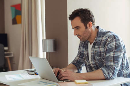 Happy young male businessman while working remotely with laptop sitting at desk at home in the kitchen
