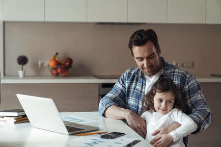 A father at work remotely with a laptop sitting at a table in his home in the kitchen and his little daughter sitting in his lap wanting attention Reklamní fotografie