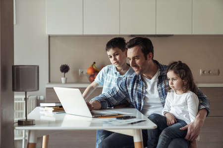 Father at work remotely with a laptop and documents sitting at a table at home in the kitchen entertains his little daughter and son