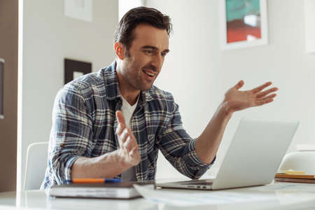 Young male businessman while working remotely with laptop sitting at desk at home in the kitchen and waving hands during video conference Reklamní fotografie