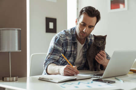 Young male businessman with his cat while working remotely with a laptop sitting at a table at home in the kitchen writes with a pencil in a notebook.