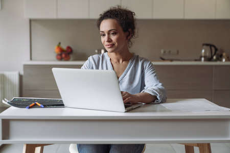 Young smiling female freelancer working at home with computer sitting at the table in the kitchen