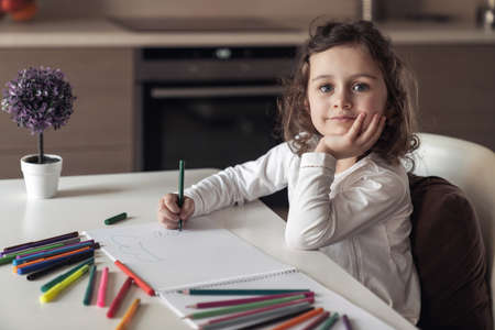 Little happy girl sitting at a table at home in the kitchen and draws a picture with colored pencils and markers Reklamní fotografie